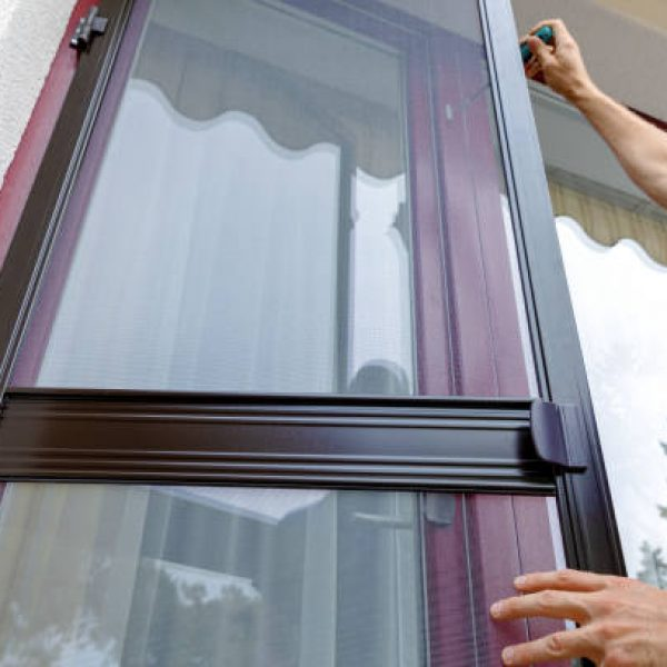 man installing mosquito net wire mesh on house balcony door